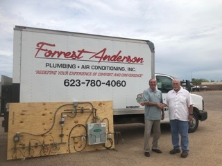 Carl Triphahn, director of P.I.P.E. (left), accepts the equipment donation from Dennis Correll of Forrest Anderson (right).