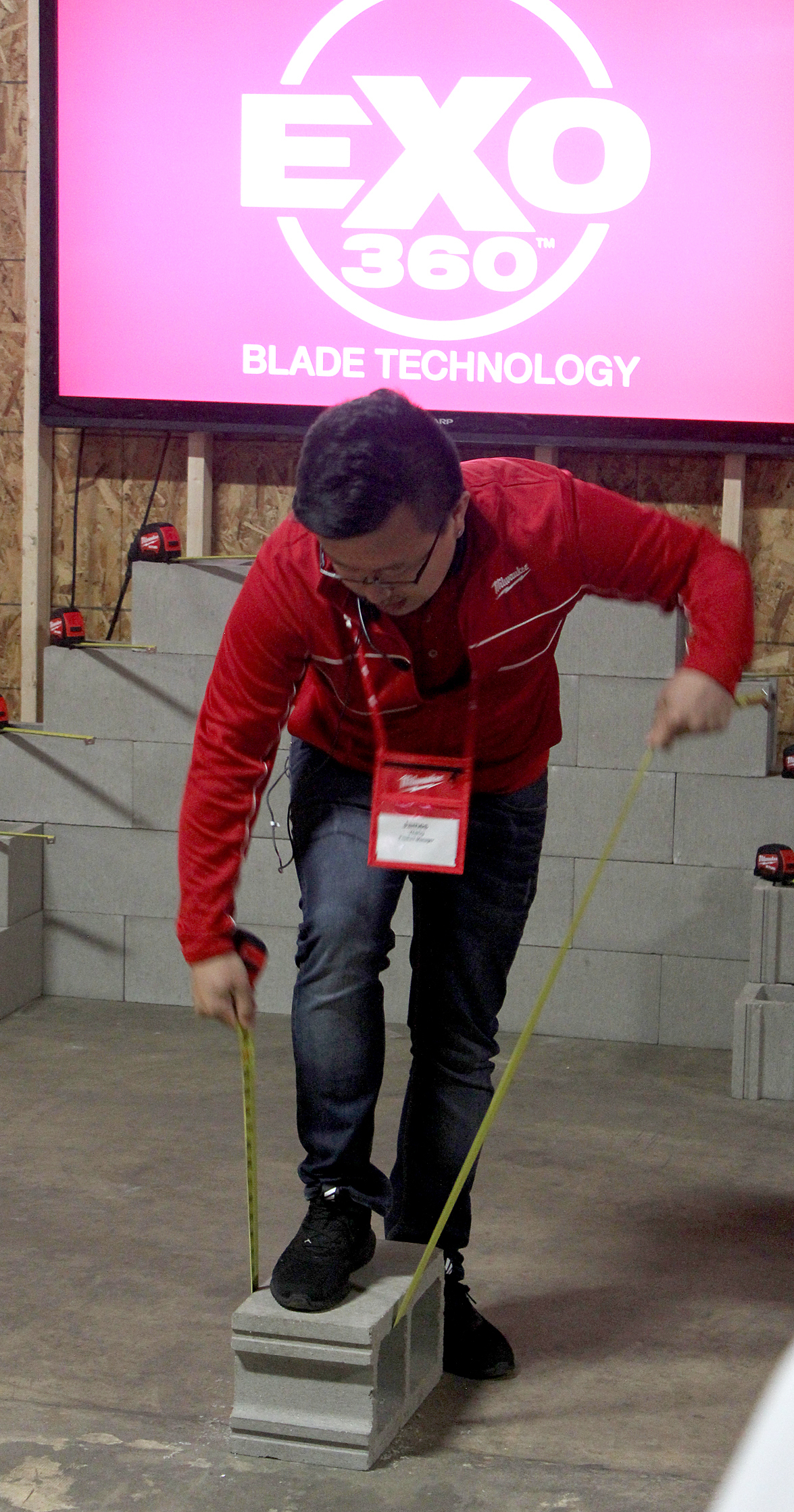 A Milwaukee Tool representative demonstrates the durability of the company's STUD measuring tape, which will be released in July.