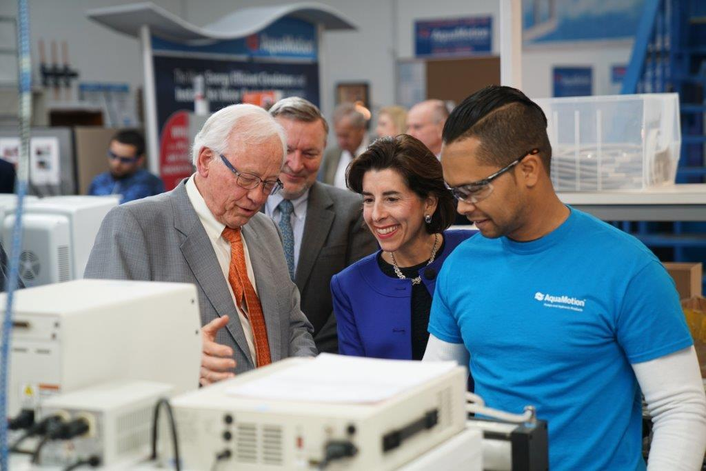 Hans Kuster, left, president of AquaMotion, and Mike McNamara, right, director of engineering, give Gov. Gina Raimondo a tour of the company's facility.