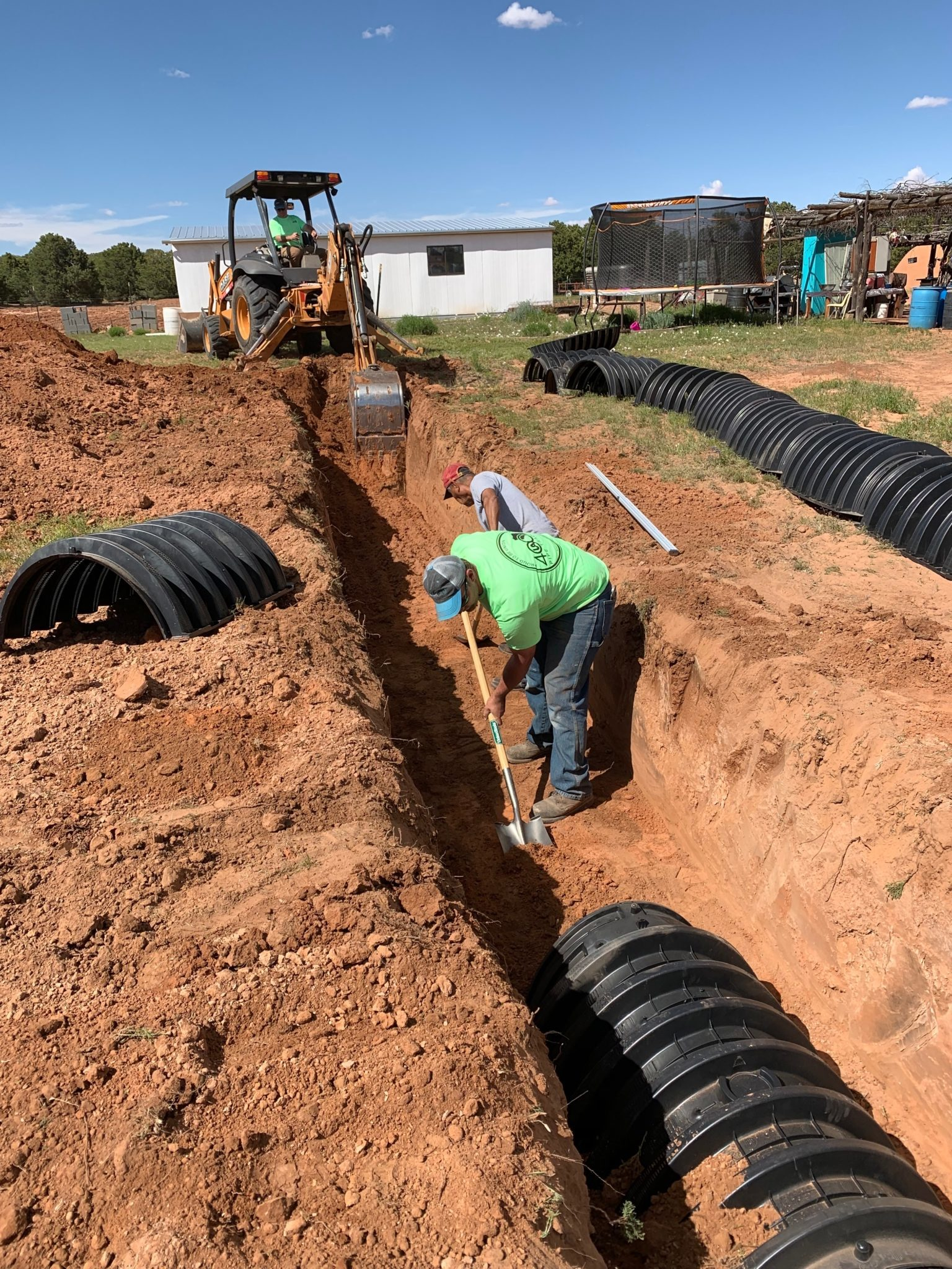 Volunteers work on installing a septic system at a home. The family of six living in the home had been relying solely on an outhouse located about 70 yards away.